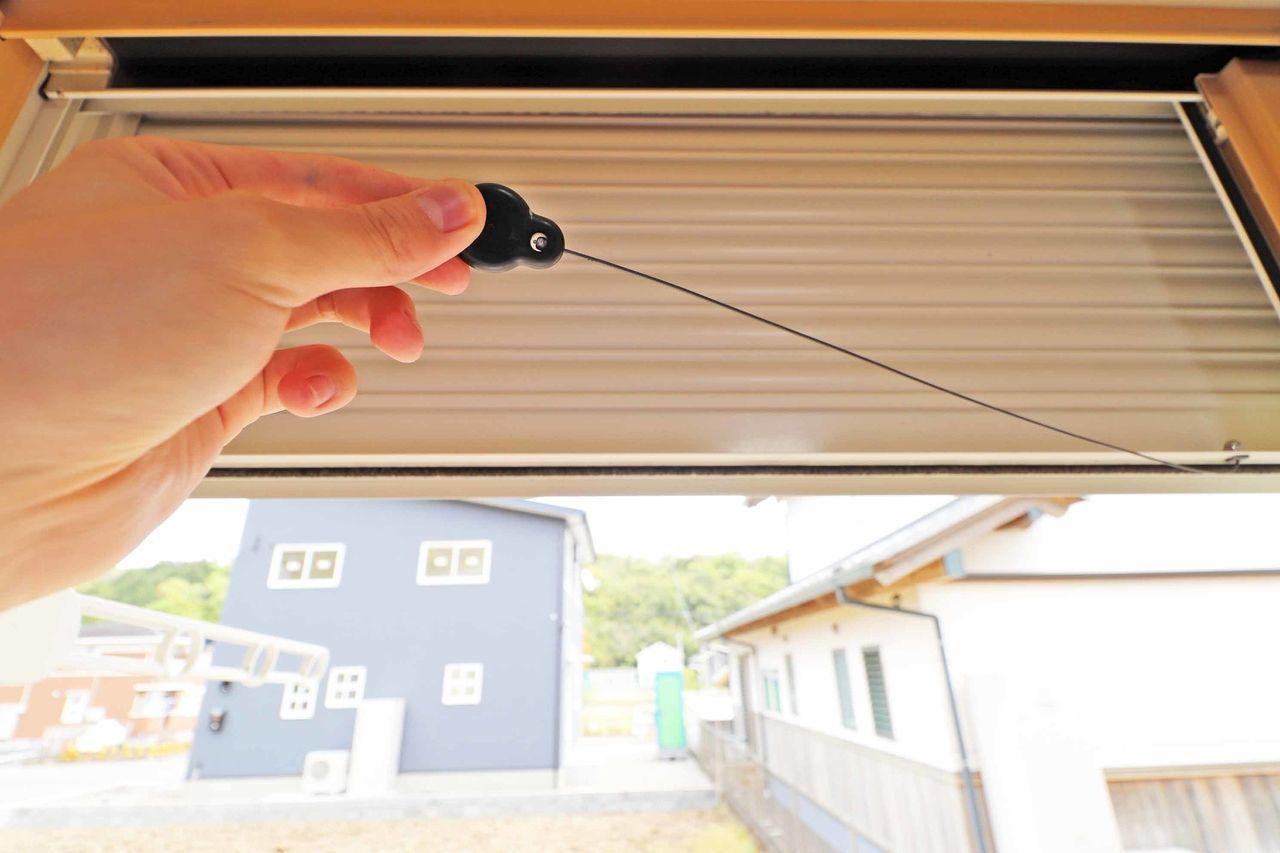 室内から紐を引っ張るだけでシャッター雨戸を使えます。黒い金物がマグネットなので普段は見えないようにできますよ。