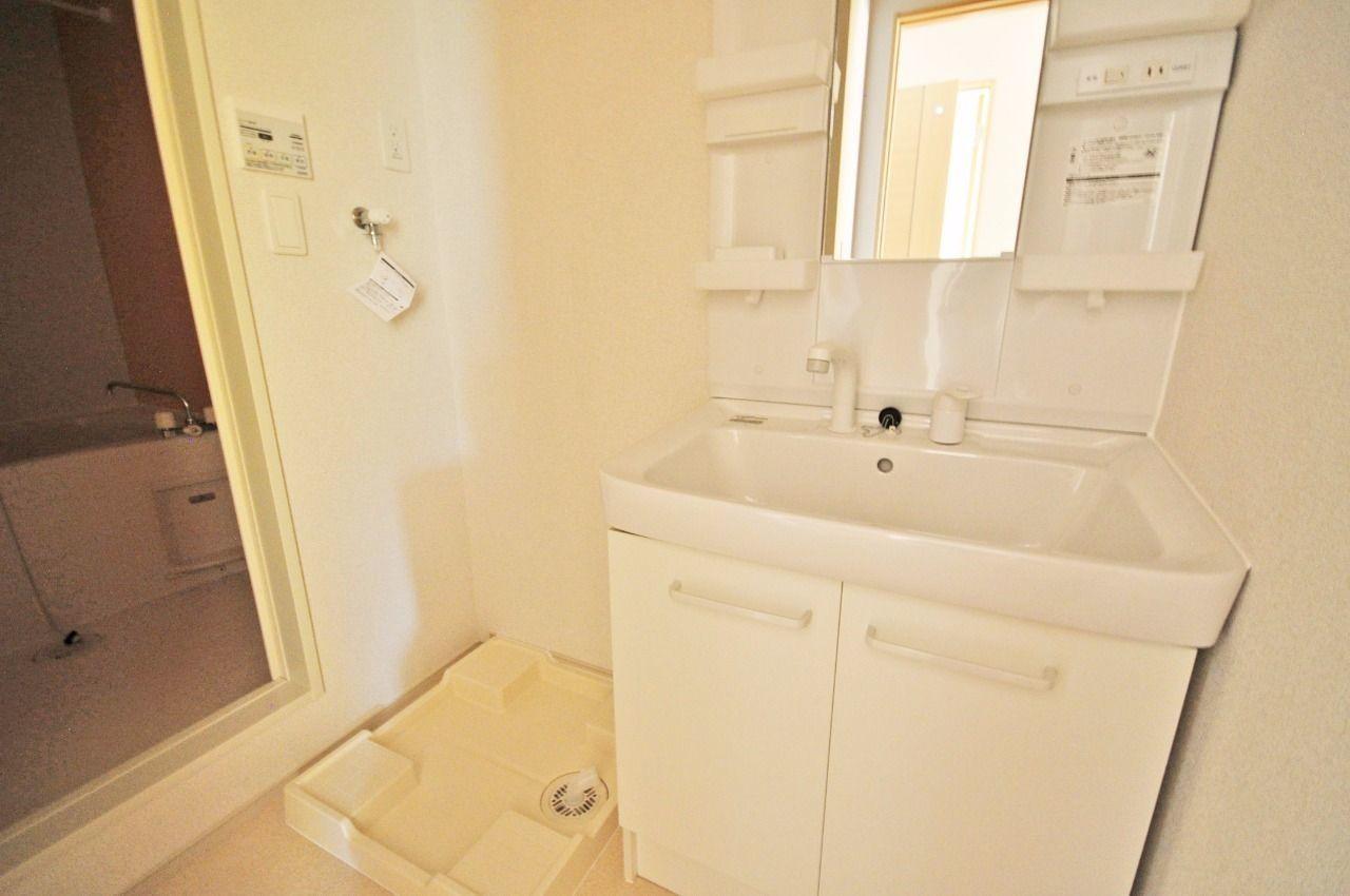 ハンドシャワー付き洗面台と洗濯機置場があります。浴室のすぐ隣にあるので便利です。