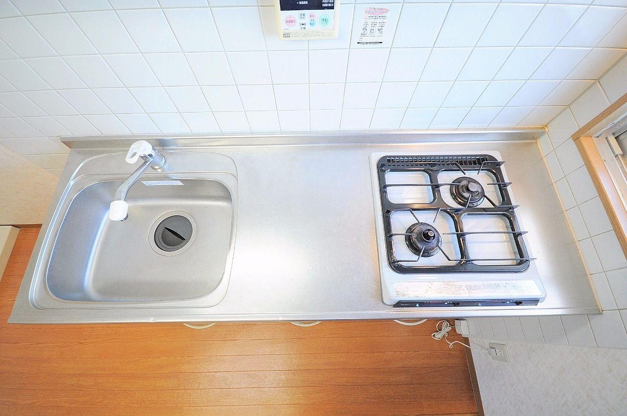 2口ガスコンロ付きのシステムキッチン。あまり大きなものではなく一人暮らし用のサイズ。