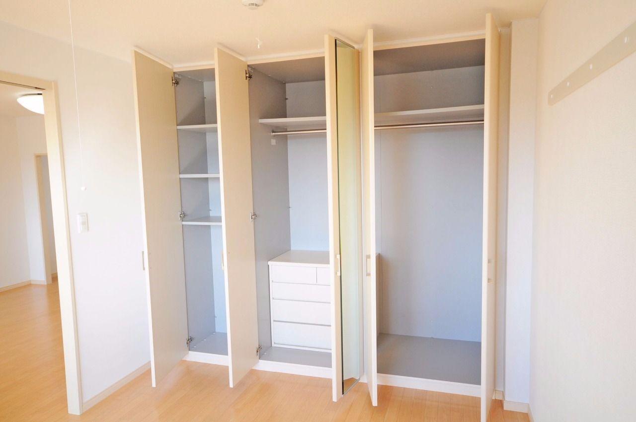 洋室の壁一面が収納。収納量が多く、タンスも備え付けで付いています。